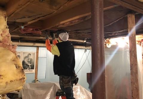 Volunteer repairing the basement ceiling