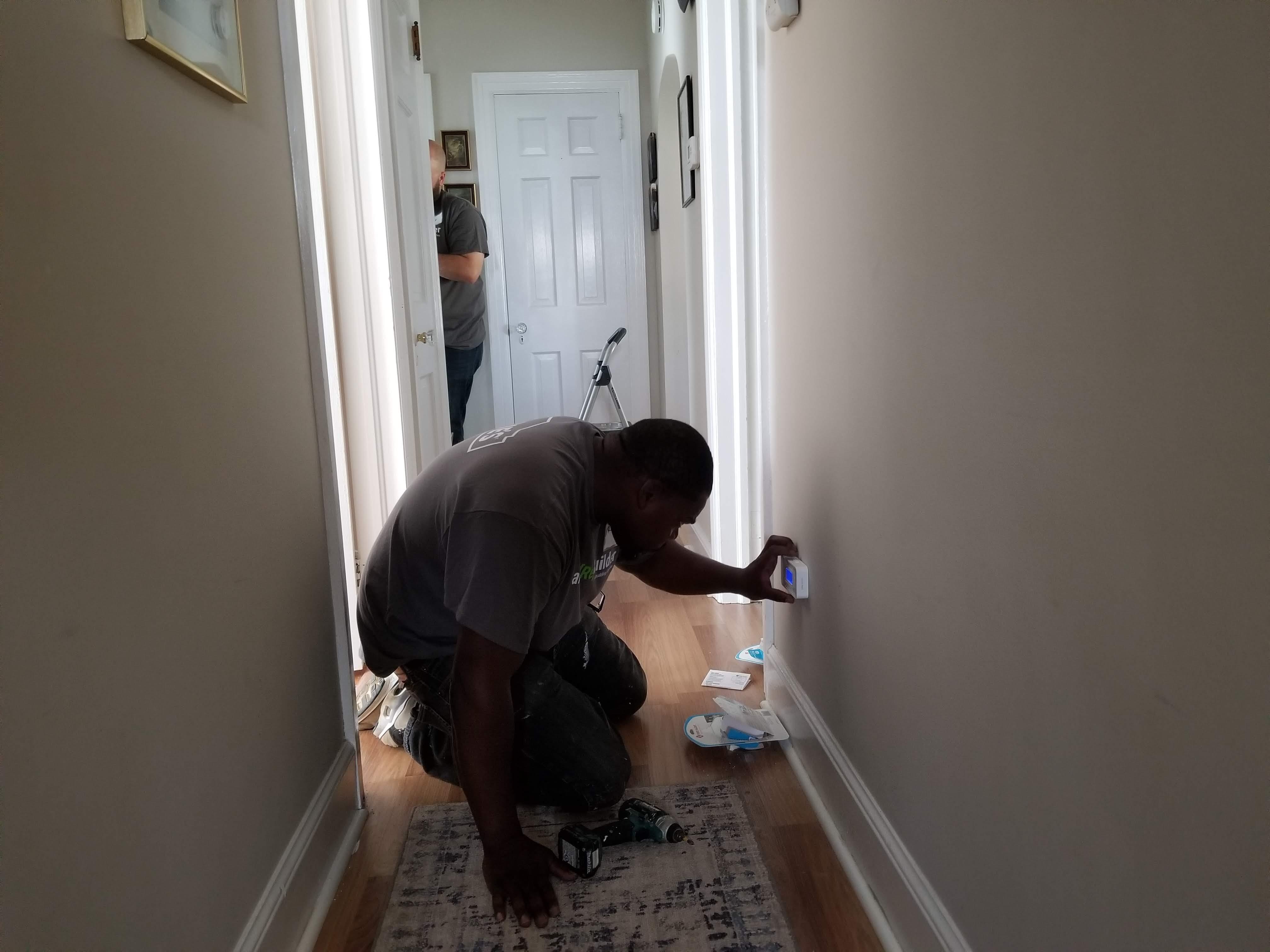 A State Farm volunteer installs a carbon monoxide alarm