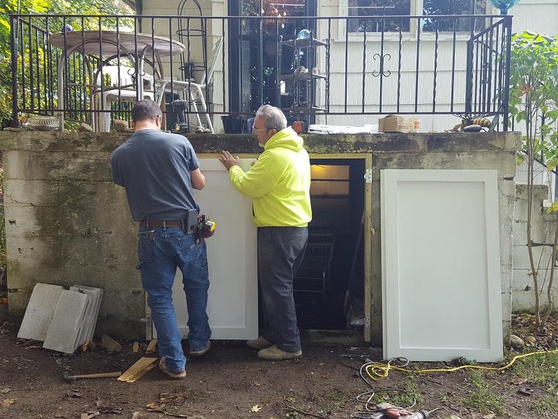 Consigli volunteers repairing a porch door.