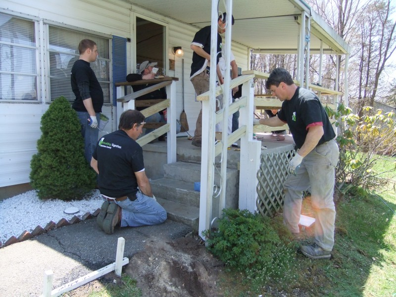 TD Bank volunteers working on a homeowner's porch