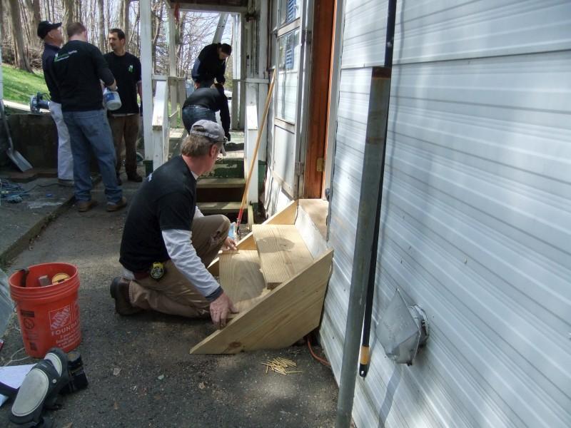 TD Bank volunteers working on a homeowner's steps
